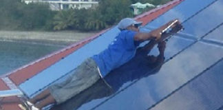 A solar installer puts in a three-rail system on St. John. (Photo provided by Caribbean Solar Company)