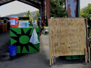 Shoppers at the Bordeaux farmers market were greeted by a sign urging sanitation and keeping a distance, and a table with all the necessities for a good hand scrub, (Source photo by S. Pennington)
