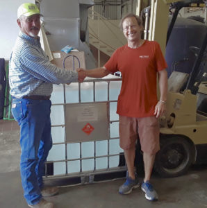 David Wallis, left, of the Limetree Bay Refinery Logistics Team, takes receipt of the first order of Breadfruit Alcohol Surface Sanitizer from Master Distiller Art Wollenweber of Mutiny Island Vodka. (Submitted photo)