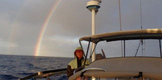 Laura Masterson smiles as she enters Caribbean waters under a rainbow on March 2. (Photo by Bruce Masterson.)