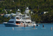 Locals paddleboard past a line of visiting yachts. (Source photo by S. Pennington)