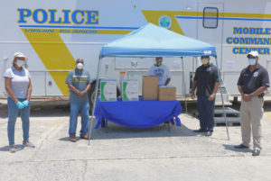 From left, Delegate Stacey Plaskett, Police Commissioner Trevor Velinor, Police Corporal Uston Cornelius, St. Croix Chief of Police Sidney Elskoe, and S\special assistant to the Chief of Police Lieutenant Walton Jack, Jr. stand in front of the VIPD's Mobile Command Unit with the food donated by actress Naturi Naughton. (Image courtesy of Delegate Stacey Plaskett's office)