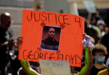 A protester holds a sign calling for justice for George Floyd during a march in Miami. Protests have taken place in cities across the country and around the world since Floyd's death while in police custody. (Shutterstock image)