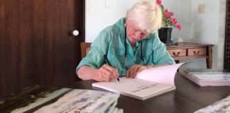 "Author and painter Emy Thomas signs copies of her new book. ""A Most Unlikely Story."" (Source photo by Susan Ellis)"